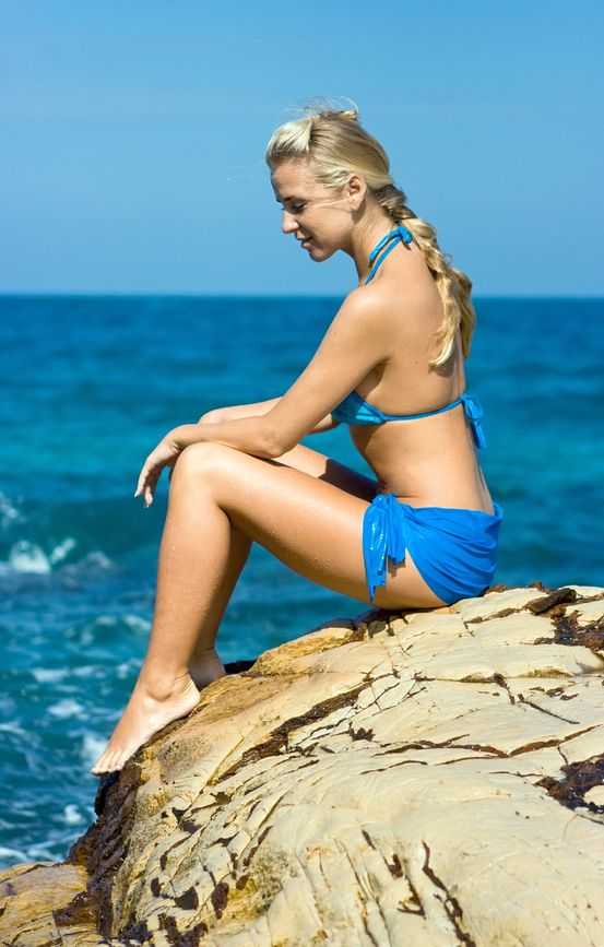 4483503 - blond girl sitting on the rock at the seaside